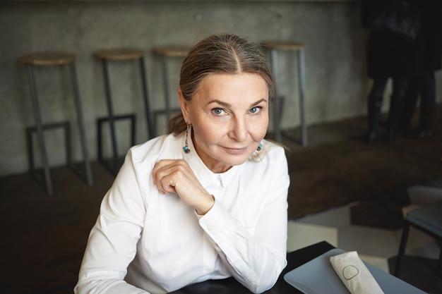Крытый снимок привлекательной кавказской женщины средних лет с голубыми глазами и очаровательной улыбкой, обедающей в кафе, в белой рубашке и стильных аксессуарах. люди, возраст, современный образ жизни и отдых