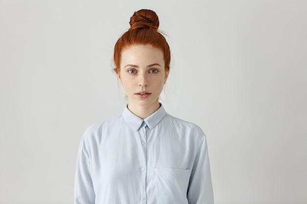 Крытый снимок привлекательной рыжей молодой женщины-офисного работника с пучком волос, позирующей на стене студии