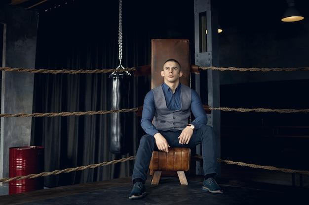 青いフォーマルなスーツを着て、ボクシングのリングの隅に座って思慮深い物思いにふける表情で見上げる魅力的な真面目なきれいな剃った若いヨーロッパの男性起業家の屋内ショット