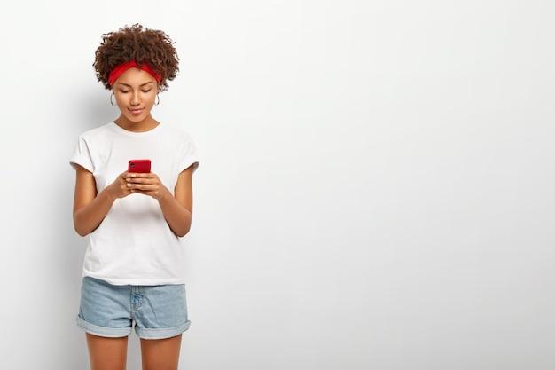 魅力的な女性の室内撮影がスマートフォンの画面を見る
