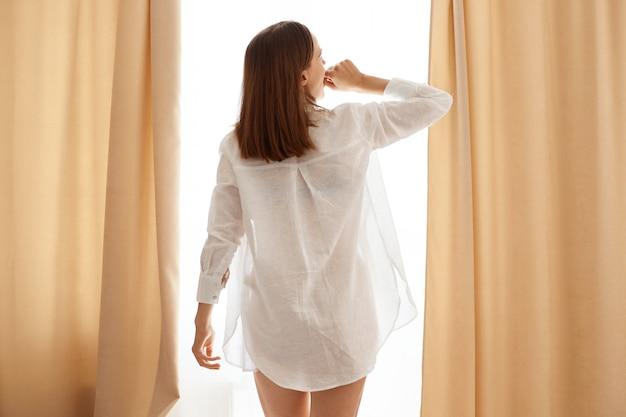 Крытый снимок привлекательной женщины в белой повседневной хлопковой рубашке, стоящей перед окном с бежевыми шторами и зевая, прикрывая рот кулаком.