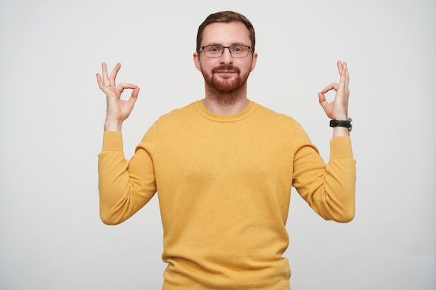 Снимок в помещении привлекательного молодого бородатого мужчины в очках с каштановыми короткими волосами, складывающими пальцы в знак мудры, во время позирования, позитивно выглядящего со спокойным лицом