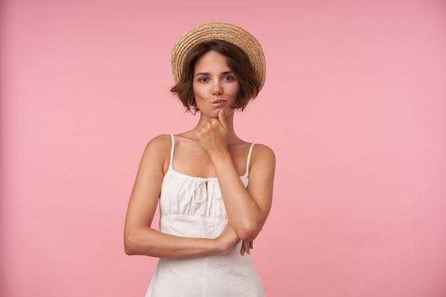 白い夏のドレスと麦わら帽子でポーズをとって、手で彼女のあごを保持し、神秘的な笑顔で見ている短い茶色の髪の魅力的な若い女性の屋内ショット
