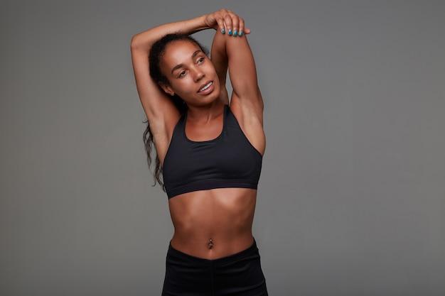 Снимок привлекательной молодой спортивной брюнетки с кудрявыми волосами в помещении с пирсингом в пупке, стоя и выполняя упражнения на растяжку для рук