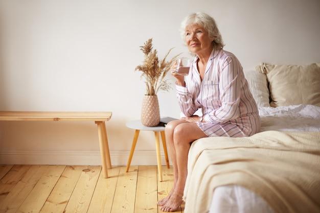 裸足で魅力的な白髪の女性年金受給者が木の床に足でベッドに座って、ガラスを持って、朝に真水を飲む屋内ショット。人、ライフスタイル、就寝時間、老化の概念