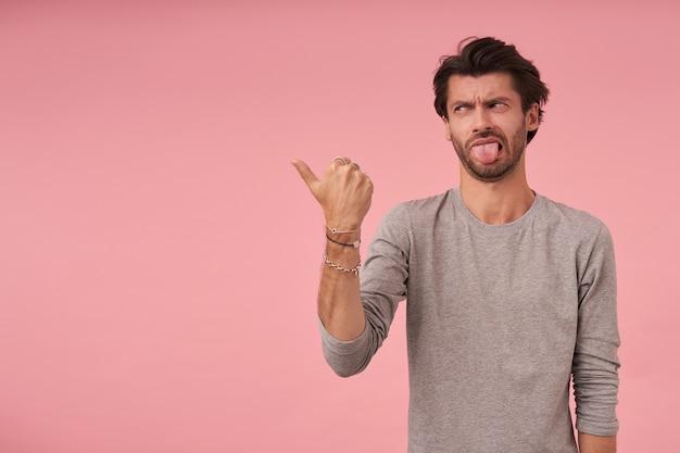 黒髪のひげを生やした若い男性の屋内ショットポーズ、カジュアルな服を着て、嫌悪感を示す顔で脇を見て、親指を上げて脇を指しています