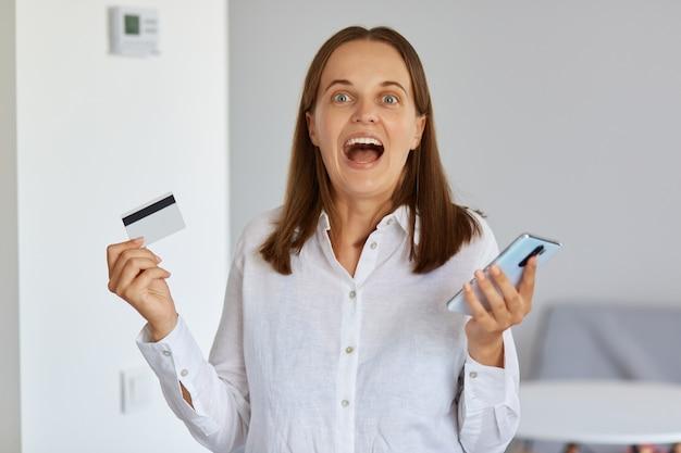 신용 카드를 손에 들고 온라인 쇼핑을 위해 스마트 폰을 사용하는 아름다운 여성의 실내 사진은 저렴한 가격과 수익성 있는 구매에 흥분합니다.