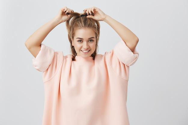 Снимок в помещении красивой, очаровательной, симпатичной молодой самки, которая поправляет свои светлые прямые волосы, широко улыбаясь, демонстрируя свои идеально белые зубы. очаровательная нежная девушка в розовом.