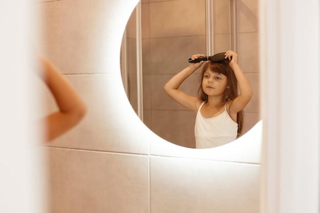 아름다운 소녀의 실내 사진은 욕실에서 머리를 빗고, 그녀의 반사를 바라보고, 흰색 캐주얼 스타일의 민소매 티셔츠를 입고, 아침 미용 절차를 하고 있습니다.