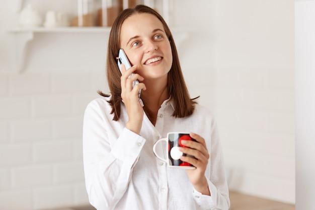 아름다운 소녀가 휴대전화로 통화하고 커피나 차 한 잔을 들고 멀리 바라보고 배경에 놓인 주방과 함께 포즈를 취하면서 웃고 있는 실내 사진.