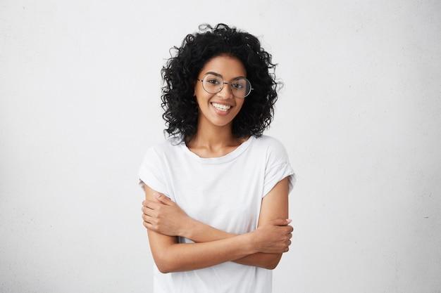 Крытый снимок красивой счастливой афро-американской женщины, весело улыбаясь, держа руки сложенными, отдыхая в помещении после утренних лекций в университете