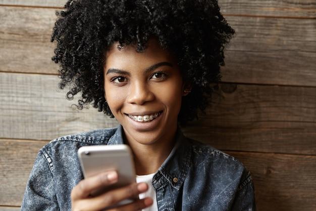 Крытый снимок красивой счастливой африканской девушки с подтяжками, смотрящей и улыбающейся в камеру