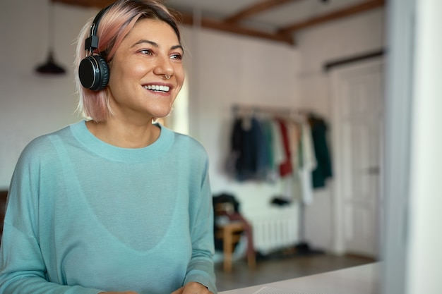 집에 앉아 온라인 시험을하는 데 무선 헤드폰을 사용하는 파란색 셔츠에 아름 다운 행복 학생 여자의 실내 샷. 사람, 교육, 학습, 기술 및 전자 기기
