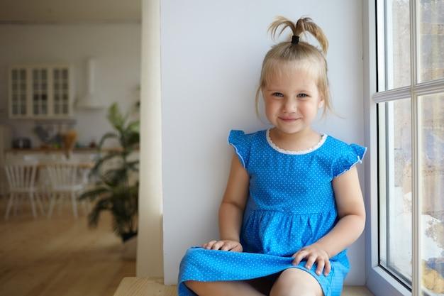 面白いポニーテールで窓辺に座って、青いドレスを着て、カメラで幸せそうに笑って、のんきな表情をして、背景にモダンなキッチンで就学前の美しい少女の屋内ショット