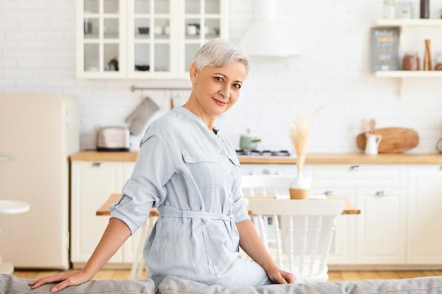 ソファの後ろに手を置いて、居心地の良いキッチンのインテリアに対してポーズをとるスタイリッシュな青いシャツの美しい成熟した灰色の髪の女性の屋内ショット。家でリラックスするエレガントな引退した女性