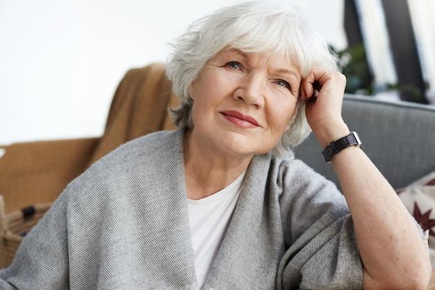 快適なソファで休んでいる短い白い髪の美しい中年白人女性の屋内ショット、悲しい物思いにふける表情、退屈な気分。人、ライフスタイル、老化の概念