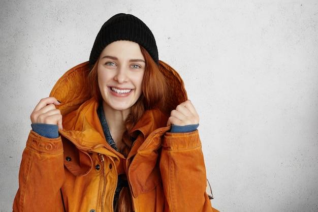 幸せそうに笑って、黒い帽子の美しい赤毛の白人少女の屋内撮影