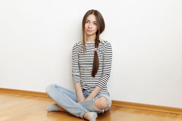 カジュアルなストライプトップを着て緩い三つ編みで厄介な髪の美しい10代の少女の屋内ショット