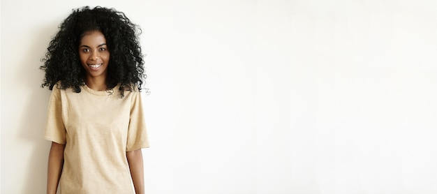 Крытый снимок красивой молодой африканской женщины с афро-прической, одетой в повседневную негабаритную футболку, радостно улыбаясь, стоя у белой глухой стены