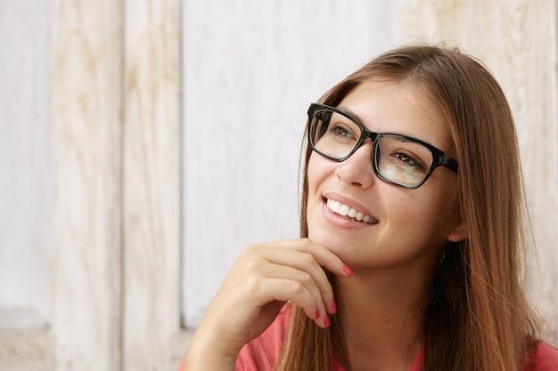 Внутренняя съемка красивой молодой кавказской деловой женщины с милой вдумчивой улыбкой, касающейся ее подбородка, с задумчивым и хитрым взглядом