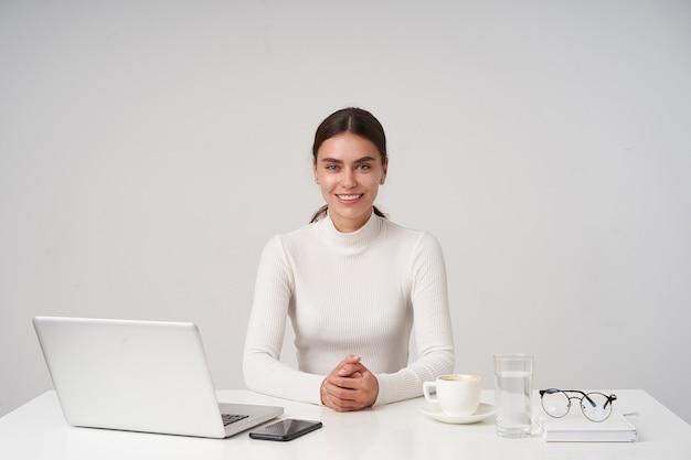 Крытый снимок красивой молодой темноволосой дамы с прической, держащей руки на столешнице и весело смотрящей в камеру с очаровательной улыбкой, изолированной на белой стене