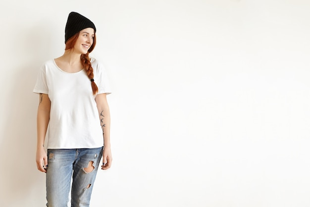 Крытый снимок красивой молодой женщины в стильной одежде, позирующей изолированной на белой стене студии