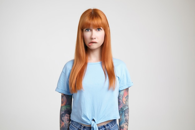 흰색 배경 위에 포즈, 카메라를 걱정스럽게 보면서 그녀의 입술을 물고 문신과 당황한 젊은 긴 머리 빨간 머리 아가씨의 실내 촬영