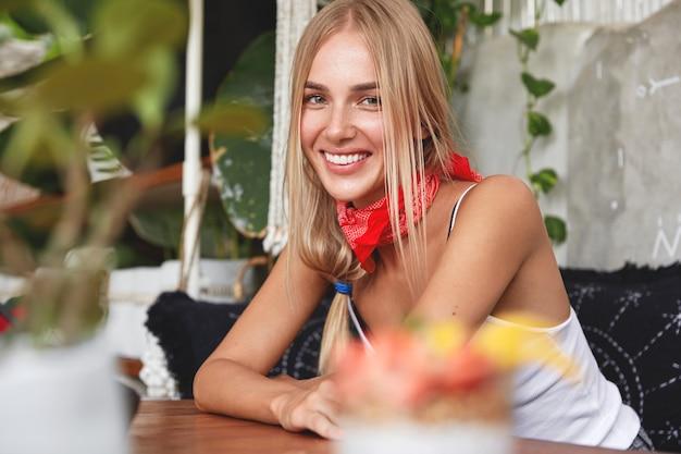 Снимок блондинки с очаровательной сияющей улыбкой в помещении, в бандане на шее, сидит на удобном диване, отдыхает в кафе