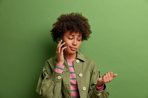 Снимок в помещении: скучающая афроамериканка разговаривает по телефону, смотрит на свой новый маникюр, расстроенное выражение лица, хорошо одетая, стоит