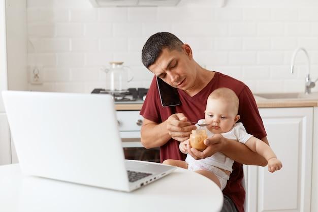 キッチンのテーブルに座って、スマートフォンを介して彼の幼児の娘にフルーツピューレを与えて話している栗色のカジュアルなスタイルのtシャツを着ているブルネットの男性の屋内ショット。