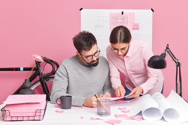 바쁜 여자와 남자의 실내 촬영은 공동 작업 공간에서 디자인 프로젝트 포즈에서 함께 작동합니다. 두 명의 건축가가 청사진으로 사무실 책상에 앉아 새 집 계획을 논의합니다. 협업 개념
