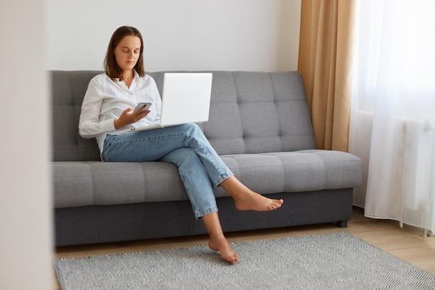 白いシャツとジーンズを着てソファに座ってラップトップを足に、フリーランサーが休憩中に電話を使用し、明るいリビングルームでポーズをとっている落ち着いた自信のある女性の屋内ショット。