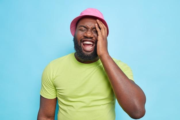 のんきなひげを生やした男の屋内ショットは、ピンクのパナマを着て笑う緑のtシャツは、青い壁に隔離された面白い何かを笑うポジティブな感情を表現します