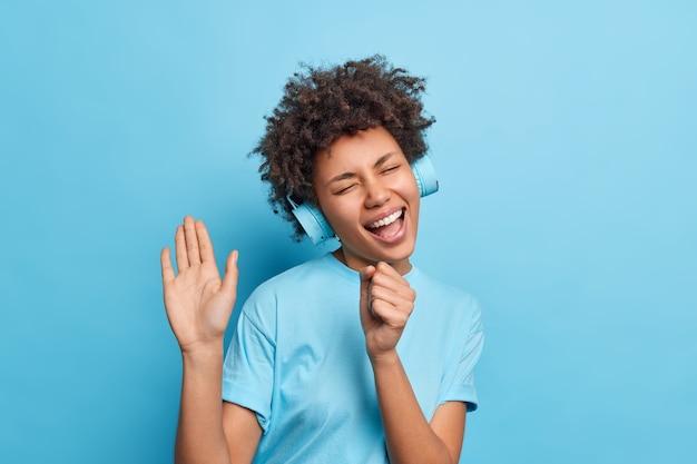 평온한 즐거운 아프리카 계 미국인 여성의 실내 촬영은 마치 마이크가 노래를 부르는 것처럼 기쁨에서 눈을 감고 파란색 벽 위에 고립 된 무선 헤드폰을 통해 음악을 듣는 것처럼 입 근처에 손을 유지합니다.