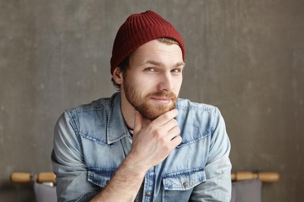 帽子とジーンズのジャケットを着ているカリスマ的な若いひげを生やした男性学生の屋内撮影
