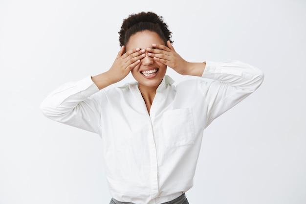 흰 셔츠를 입은 매력적인 평온한 아프리카 계 미국인 여성 고용주의 실내 촬영, 손바닥으로 눈을 가리고, 픽-어-부 게임 중 눈이 멀고 회색 벽 위에 크게 웃고 있음