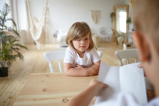 家の木製のテーブルに座って、紙を持っている認識できない若い父親と一緒に宿題をチェックしている魅力的なかわいい女の子の屋内ショット。子供の顔に選択的な焦点