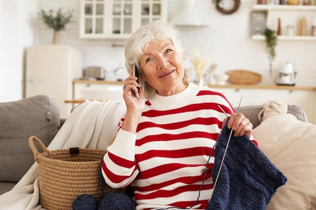 自宅で余暇を楽しんでいる白髪の魅力的なヨーロッパの引退した女性の屋内ショット、針を使って息子のためにセーターを編んで、電話で会話しています。モバイルで話している幸せな年配の女性