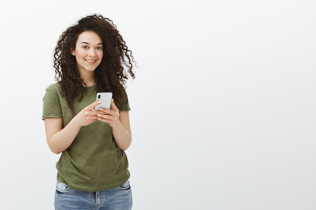 Снимок очаровательной кокетливой кудрявой сотрудницы в помещении в повседневной футболке