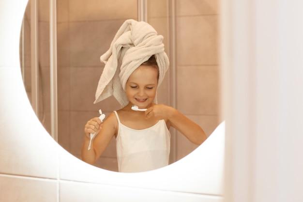 Крытый снимок очаровательной маленькой девочки, чистящей зубы в ванной, стоя перед зеркалом, выжимающей зубную пасту из тюбика и счастливо улыбаясь.