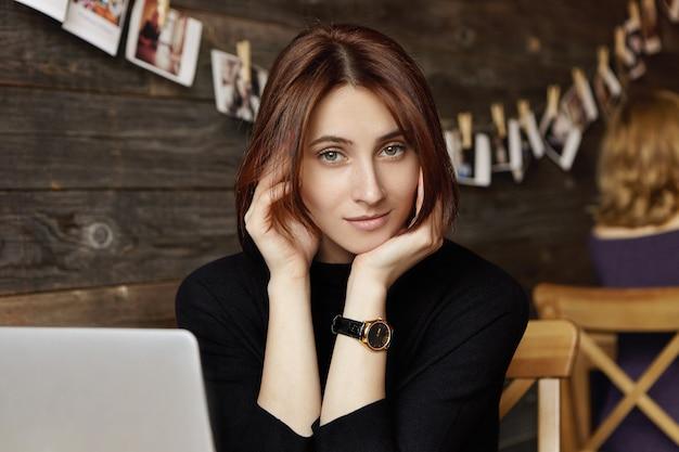 黒のドレスを着ているチョコレートの髪を持つ魅力的な若い女性の屋内ショット