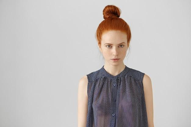 生姜の髪をまんじゅうで着ているヨーロッパ風の魅力的な若い女性の屋内ショット