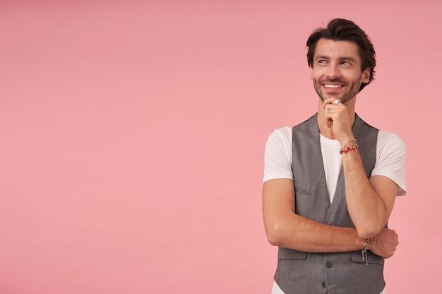 회색 양복 조끼와 흰색 티셔츠를 입고 분홍색 배경 위에 포즈를 취하고 손으로 턱을 잡고 매력적인 미소로 옆으로 보는 트렌디 한 헤어 스타일로 쾌활한 수염 난 남성의 실내 샷