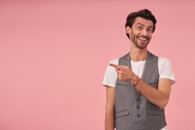 人差し指で脇を向いて、灰色のチョッキと白いtシャツを着て、広い笑顔で見ているトレンディなヘアカットを持つ陽気なひげを生やした若い男性の屋内ショット