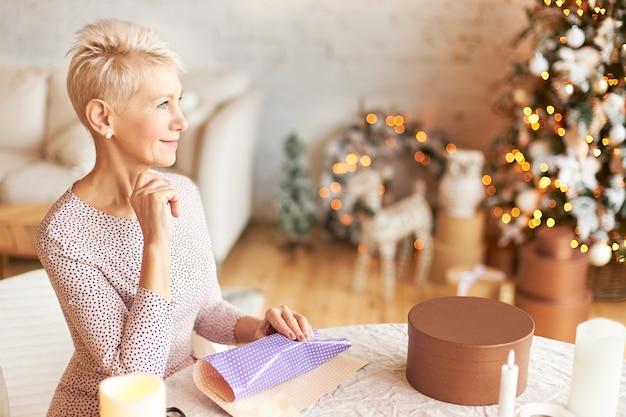 쾌활한 성숙한 짧은 머리 유럽 여성의 실내 샷, 새해 또는 크리스마스 축하를 준비, 테이블에 선물 종이와 함께 거실에 앉아 잠겨있는 사려 깊은 표정을 갖는 미소