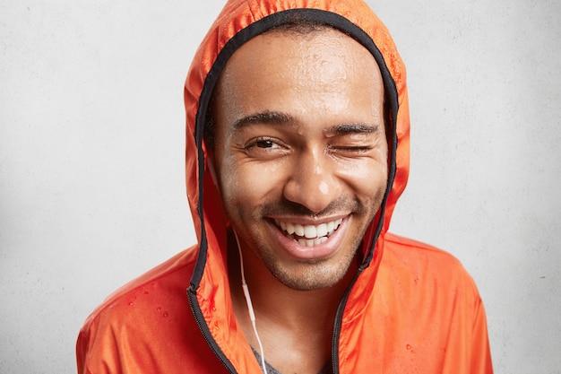 スポーツに行った後に濡れている健康な純粋な肌を持つ陽気な肯定的な混血男の屋内撮影