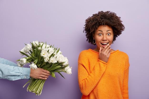 쾌활한 놀란 어두운 피부 여자의 실내 촬영은 낯선 사람으로부터 꽃을받습니다.