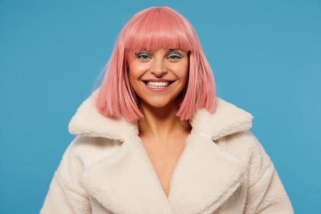 派手な服を着て、広い笑顔で幸せそうに見えるお祝いの化粧をした陽気な若いピンクの髪の女性の屋内ショット