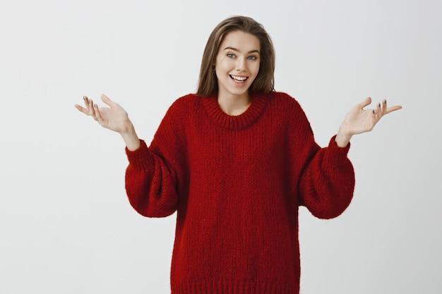 Внутренний снимок невежественной привлекательной дружелюбной европейской женщины в модном красном свободном свитере, пожимающей плечами с распростертыми ладонями, объясняющей что-то, стоящей в неведении и допрошенной