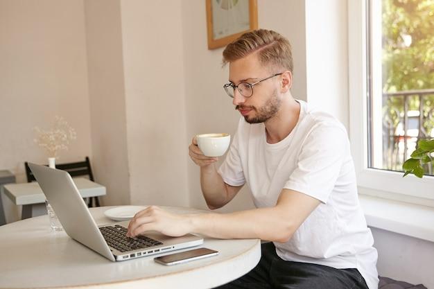 Снимок в помещении: сосредоточенный молодой симпатичный мужчина в белой футболке, работающий за ноутбуком в кафе, пьющий кофе и задумчиво смотрящий на экран